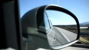 Vista ascendente cercana del espejo del lado del coche durante la impulsión de la carretera almacen de metraje de vídeo