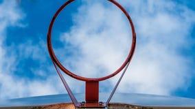 Vista ascendente da aro de basquetebol contra um céu azul brilhante imagem de stock