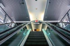 Vista ascendente da una scala mobile con i corrimani di vetro fotografie stock libere da diritti