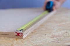 Vista ascendente próxima da madeira de medição da mão de um homem com uma fita handyman medida fotos de stock