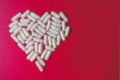Vista ascendente próxima das cápsulas brancas que formam um coração no fundo vermelho com espaço fotografia de stock royalty free
