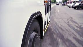 Vista ascendente próxima das rodas e dos pneus na estrada de uma equitação do ônibus em torno da cidade cena O ônibus branco abai video estoque