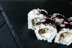 Vista ascendente próxima em rolos de sushi com com os peixes, quiabo e queijo vermelhos de Philadelphfia em uma placa de carvão p fotos de stock royalty free