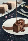 Vista ascendente próxima na sobremesa fresca do chocolate que derrama o chocolate quente em um fundo escuro Alimento do voo Movim imagem de stock