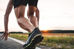 Vista ascendente próxima nos pés fortes e musculares do corredor do atleta na pose do começo na estrada asfaltada exterior imagem de stock royalty free