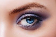Vista ascendente pr?xima do olho azul da mulher com m?scaras bonitas e composi??o preta do l?pis de olho foto de stock
