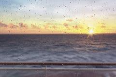 Vista astratta delle goccioline della finestra contro il tramonto e l'oceano fotografia stock