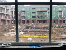 Vista através da janela dos homens que constroem a piscina Imagens de Stock Royalty Free