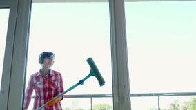 Vista através da janela, mulher de sorriso nos fones de ouvido, nas luvas, limpeza, janela da lavagem pelo espanador especial, ap filme