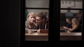Vista através da janela Pares bonitos novos que sentam-se no café e na fala Data romântica dentro na cidade na noite vídeos de arquivo