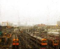Vista através da janela riscada com os pingos de chuva nos trens estacionados em trilhas perto de Brisbane Austrália fotografia de stock