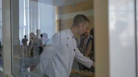 A vista através da mulher de vidro toma o garçom Recommends Drinks do bolo vídeos de arquivo