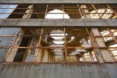 Vista através das janelas quebradas de uma construção industrial abandonada demulida Foto de Stock Royalty Free
