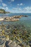 Vista através das rochas e dos seixos, praia de Porthpean, Cornualha imagem de stock royalty free