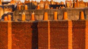 Vista através de Roofscape de chaminés e de Chimneypots Redbrick e da terracota foto de stock