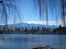 Vista através de um lago às montanhas cobertos de neve Imagem de Stock Royalty Free