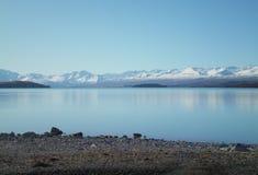 Vista através de um lago azul às montanhas neve-tampadas Fotografia de Stock