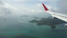 Vista através de uma janela do avião na ilha, no oceano, no céu e nas nuvens tropicais filme