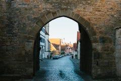 Vista através do arco a uma rua bonita com as casas alemãs tradicionais no der Tauber do ob de Rothenburg em Alemanha imagem de stock