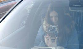 Vista através do para-brisa do carro na mulher moreno nova para baixo no revestimento azul que olha o telefone imagem de stock