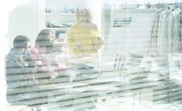 Vista attraverso i ciechi un gruppo di stilisti in uno studio moderno immagini stock libere da diritti