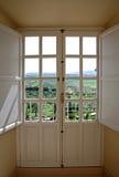 Vista attraverso i portelli di legno alla campagna Fotografie Stock