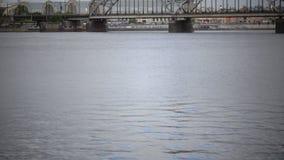 Vista attraverso il fiume di Daugava del ponte ferroviario di Riga e la costruzione dell'accademia delle scienze della Lettonia,  archivi video