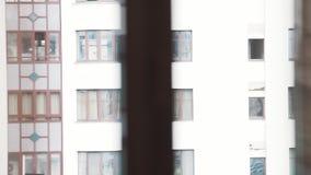 Vista attraverso il vetro di finestra sulle facciate di grande nuova alta costruzione bianca archivi video