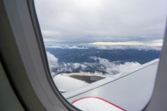 Vista attraverso la finestra in aereo di linea nell'aria fotografia stock