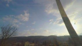 Vista attraverso la finestra del treno, cielo blu soleggiato con le nuvole, alberi, colline sull'orizzonte video d archivio