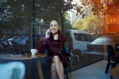 Vista attraverso la finestra di una donna con il sorriso sveglio che ha conversazione di telefono cellulare mentre riposando dopo Immagini Stock Libere da Diritti