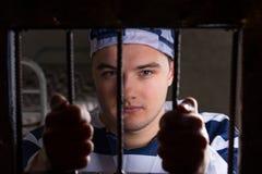 Vista attraverso la porta del ferro con le barre della prigione sul giovane prigioniero maschio h Immagine Stock Libera da Diritti