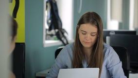 Vista attraverso lo scaffale sulle donne che lavorano con i documenti archivi video