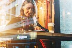 Vista attraverso vetro Giovane donna sorridente di affari che si siede in caffè alla tavola, al caffè bevente e per mezzo del com Fotografie Stock Libere da Diritti