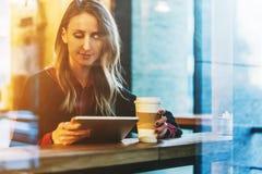 Vista attraverso vetro Giovane donna sorridente di affari che si siede in caffè alla tavola, al caffè bevente e per mezzo del com Immagine Stock