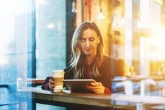 Vista attraverso vetro Giovane donna sorridente di affari che si siede in caffè alla tavola, al caffè bevente e per mezzo del com Fotografie Stock