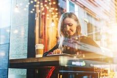 Vista attraverso vetro Giovane donna sorridente di affari che si siede in caffè alla tavola, al caffè bevente e per mezzo del com Fotografia Stock