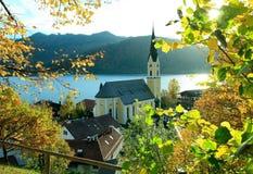Vista autunnale attraverso i rami al lago ed alla chiesa di schliersee Fotografia Stock Libera da Diritti