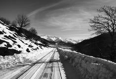 Vista in bianco e nero sulla strada della neve in montagna di mattina di inverno Fotografia Stock