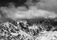 Vista in bianco e nero sulle alte montagne nevose in nuvole a soleggiato Fotografie Stock