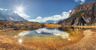 Vista bonita com as rochas altas com picos cobertos de neve, lago da montanha Fotos de Stock