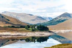 Vista bonita com a casa escocesa nas montanhas lago e floresta Fotografia de Stock
