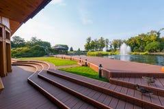Vista bonita da plataforma de madeira com os patos que andam ao longo dela à fonte que bate o meio da lagoa Fotos de Stock