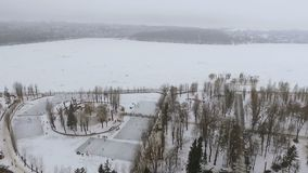 Vista bonita do ar a um parque do inverno e a um lago congelado Os povos relaxam no ar livre, patim, pescadores travam filme