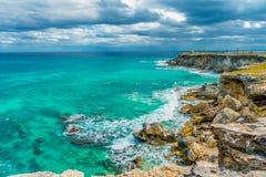 A vista bonita do penhasco rochoso e a turquesa molham no nascer do sol o na parte do sul de Isla Mujeres nas Caraíbas imagens de stock