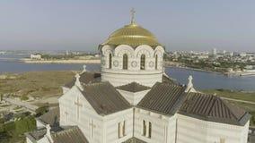 Vista bonita do templo grande do russo no banco de rio perto da cidade tiro Vista da igreja branca com abóbadas douradas sobre filme