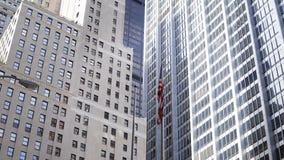 Vista bonita dos arranha-céus de vidro em New York, EUA Bandeira americana nacional que acena no vento vídeos de arquivo