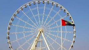 A vista bonita dos UAE embandeira a ondulação na frente da roda do olho do porto