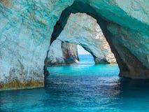 A vista bonita em cavernas azuis balança arcos do barco sightseeing com os turistas na água azul do mar Ionian dentro da caverna  fotografia de stock