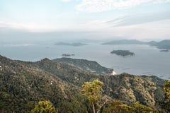 Vista bonita em florestas e em explorações agrícolas do céu nebuloso e da pérola da montagem Misen na ilha de Miyajima em Hiroshi foto de stock